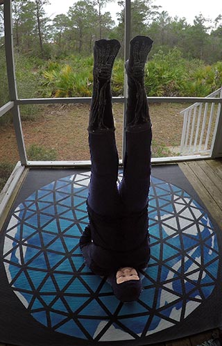 'To Solstice' position on Fuller Dome Yoga Mat on the porch at Outer Solstice 2018 retreat in cloudy 50° weather
